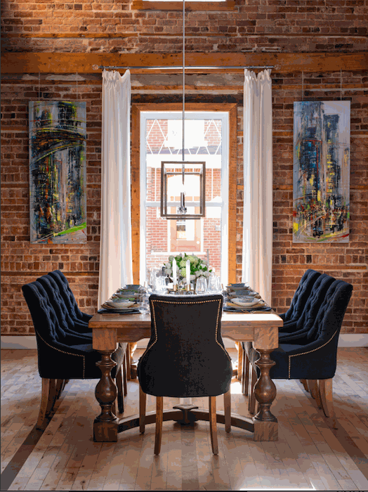 <img src=&quot;dining room.jpg&quot; alt=&quot;Dining room with brick walls, wooden customized dining table, and navy blue upholstered chairs.&quot;>