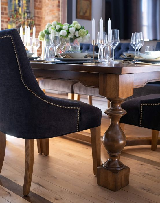 <img src=&quot;dining chair&quot; alt=&quot;side view of an upholstered, navy blue dining chair beside a wooden dining table laden with glassware and chinaware&quot;>