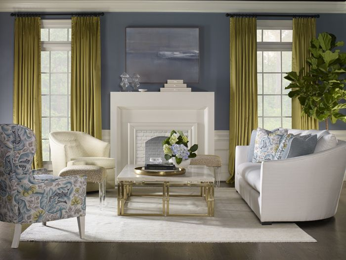 <img src=&quot;living room&quot; alt=&quot;living room designed with a white, concrete fireplace; white sofa; one white chair; one printed chair; metal and stone center table; and other design elements&quot;>